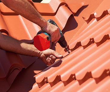 mężczyzna przykręca płytki dachowe